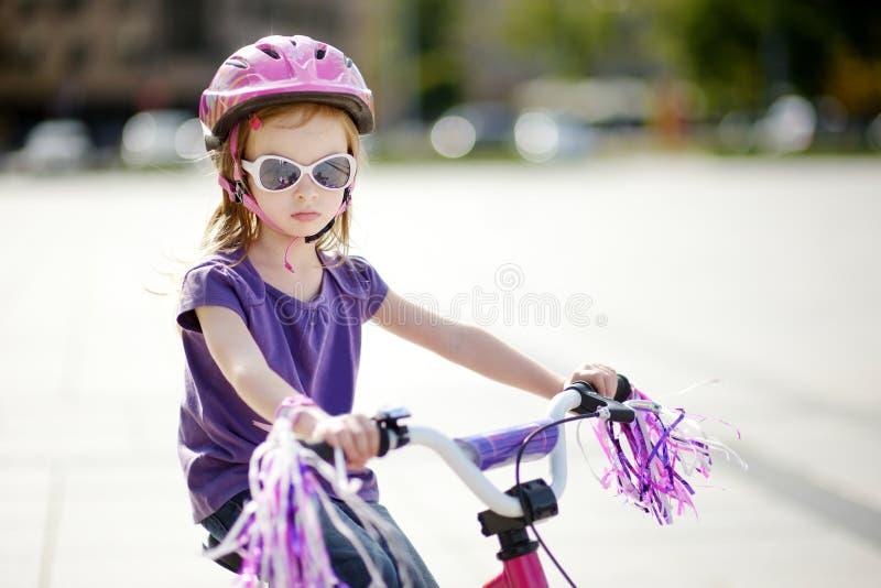 Aanbiddelijk meisje die een fiets berijden royalty-vrije stock afbeeldingen