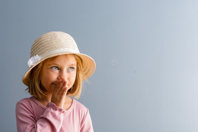 Aanbiddelijk meisje die een geheim fluisteren royalty-vrije stock afbeelding