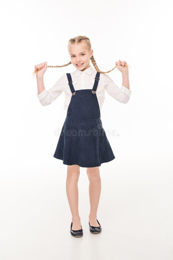 aanbiddelijk meisje die haar vlechten houden en bij camera glimlachen stock afbeeldingen
