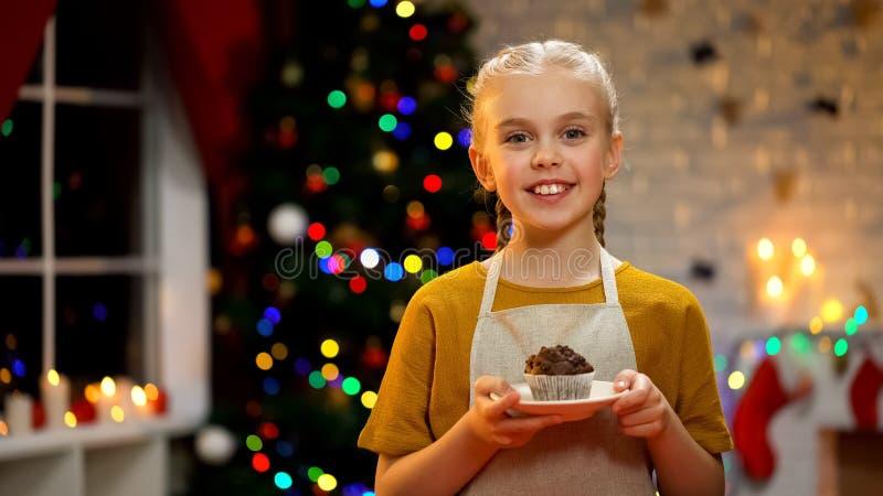 Aanbiddelijk meisje die met muffin aan camera, de gelukkige atmosfeer van de Kerstmisvooravond glimlachen stock foto's