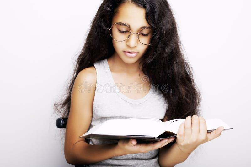 Aanbiddelijk meisje die met oogglazen en boek bestuderen royalty-vrije stock fotografie
