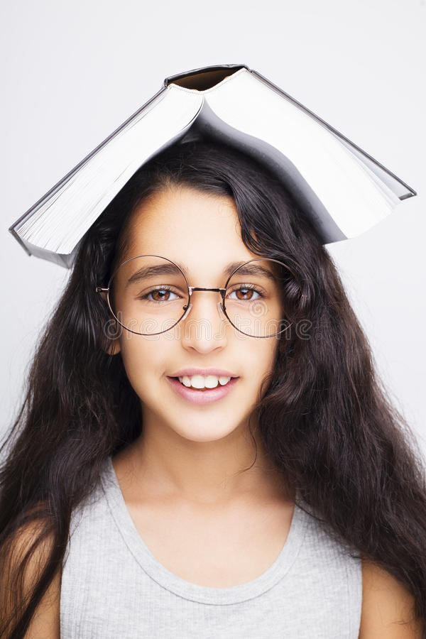 Aanbiddelijk meisje die met oogglazen en boek op het hoofd bestuderen stock afbeelding