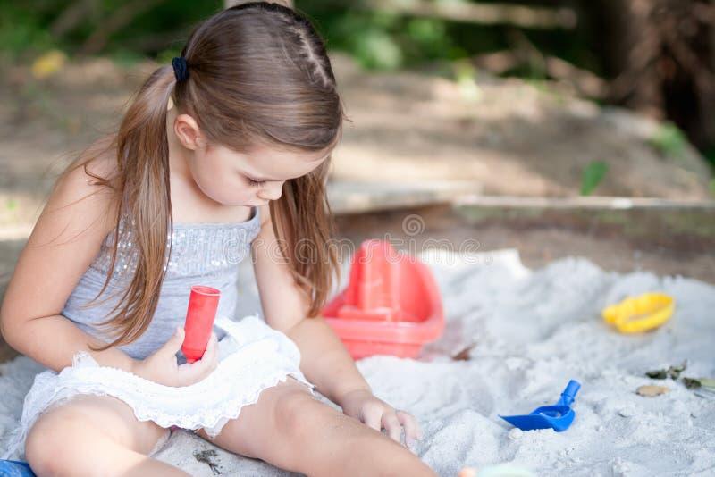Aanbiddelijk meisje die met twee varkensstaarten in zandbak in in de schaduw gestelde binnenplaats spelen royalty-vrije stock foto