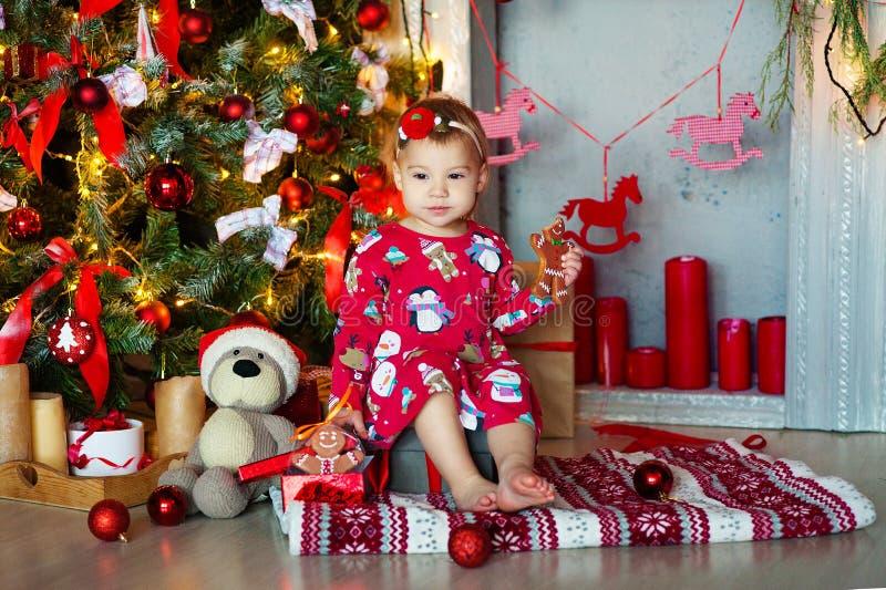 Aanbiddelijk meisje die peperkoekcake eten binnenshuis tijdens het seizoen van de Kerstmisvakantie royalty-vrije stock foto's