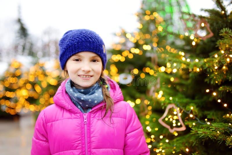 Aanbiddelijk meisje die prachtige tijd op traditionele Kerstmismarkt hebben stock afbeelding