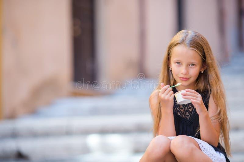 Aanbiddelijk meisje die roomijs eten in openlucht bij de zomer Leuk jong geitje die van echte Italiaanse gelato in Rome genieten royalty-vrije stock foto's