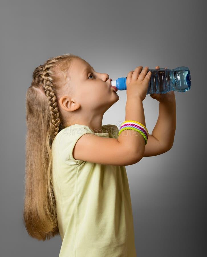 Aanbiddelijk meisje die vers schoon water van plastic fles op grijs drinken royalty-vrije stock afbeeldingen