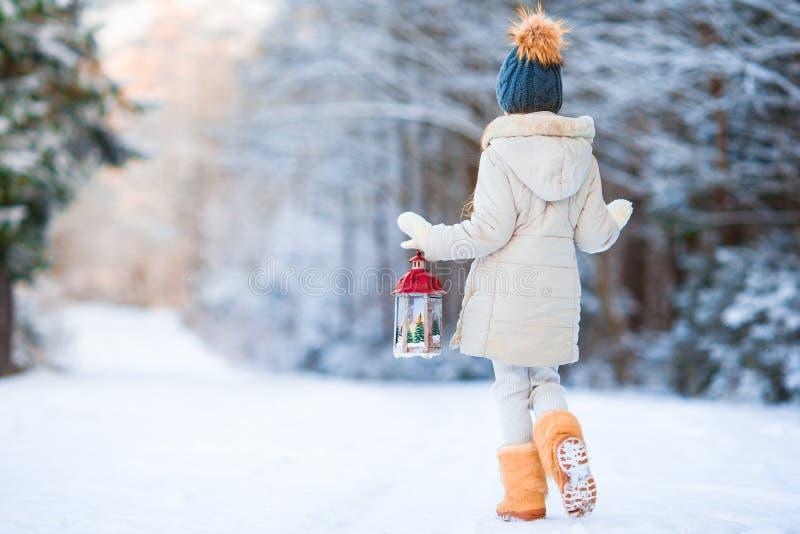 Aanbiddelijk meisje die warme laag in openlucht op de holdingsflitslicht van de Kerstmisdag dragen stock foto's
