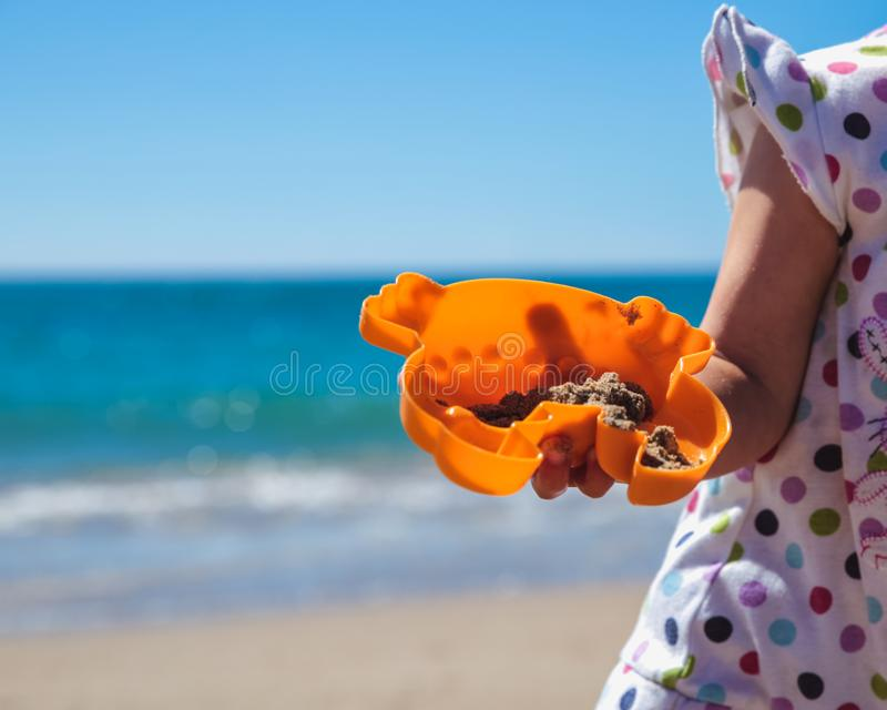 Aanbiddelijk meisje die zandkasteel maken bij strand royalty-vrije stock fotografie