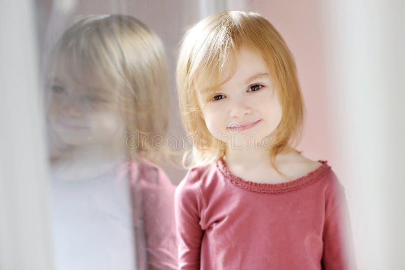 Aanbiddelijk meisje door het venster royalty-vrije stock afbeeldingen