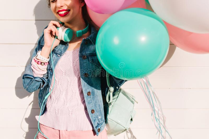Aanbiddelijk meisje in gebreid roze sweater en denimjasje die graag met kleurrijke heliumballons stellen van gebeurtenis Het glim stock foto