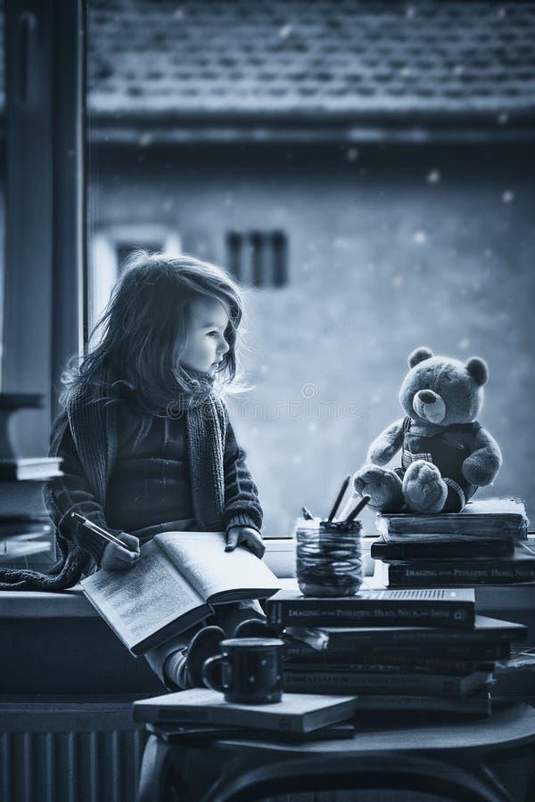Aanbiddelijk meisje, het schrijven brief aan Kerstman, die op een wind zitten royalty-vrije stock afbeeldingen
