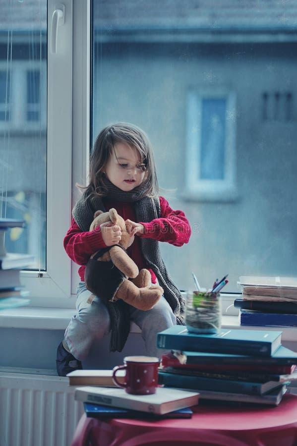 Aanbiddelijk meisje, het schrijven brief aan Kerstman, die op een wind zitten stock foto