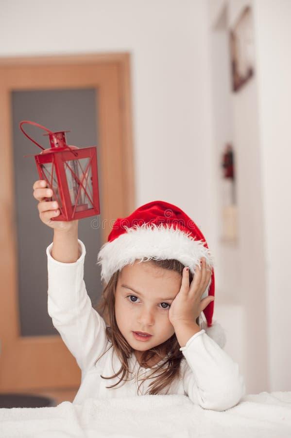Aanbiddelijk meisje met een in hand Kerstmislantaarn, wachtend F stock afbeelding