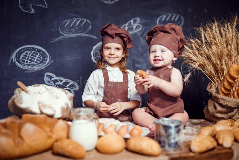 Aanbiddelijk meisje met kind bij lijst het koken stock foto's