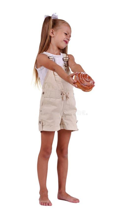 Aanbiddelijk meisje weerzinwekkend met suikerachtig broodje dat op een witte achtergrond wordt geïsoleerd Jong geitje die ongezon stock afbeeldingen