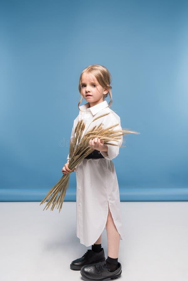 Aanbiddelijk meisje in witte de tarweoren van de kledingsholding en het bekijken camera stock foto