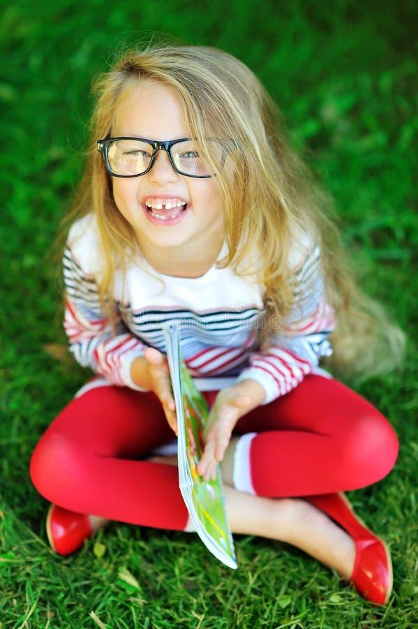 Aanbiddelijk meisjeholding boek en het lachen stock foto's