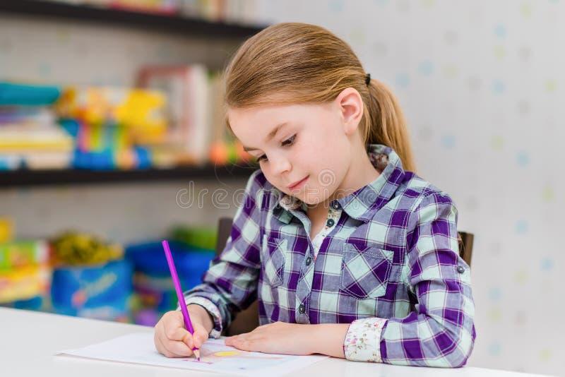 Aanbiddelijk nadenkend meisje met blonde haarzitting bij lijst en tekening met purper potlood royalty-vrije stock foto's