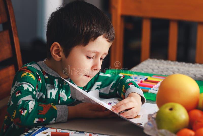 Aanbiddelijk opent weinig jongen pagina van oefenboek Leuke jongen readin stock foto
