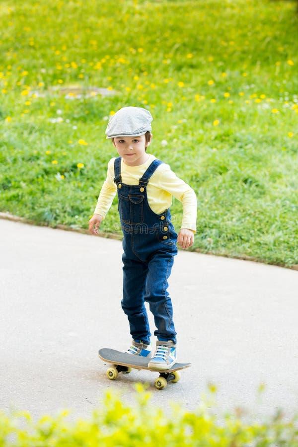 Aanbiddelijk peuterkind, die op de straat met een skateboard rijden royalty-vrije stock foto