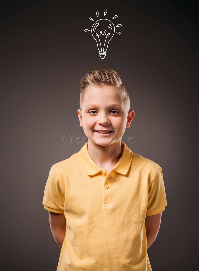 aanbiddelijk preteen glimlachende jongen met getrokken gloeilampenidee, stock foto's