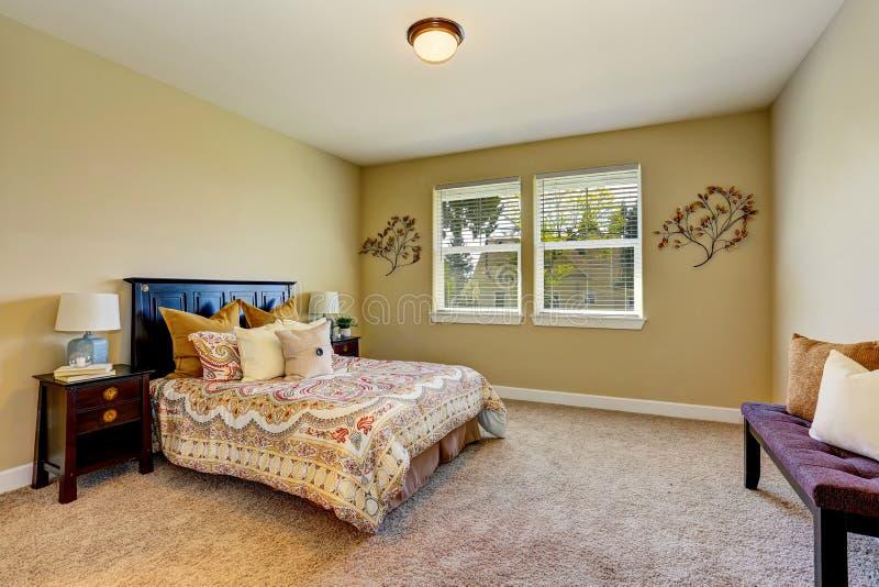 Aanbiddelijk slaapkamerbinnenland met beige muren, houten meubilair stock foto