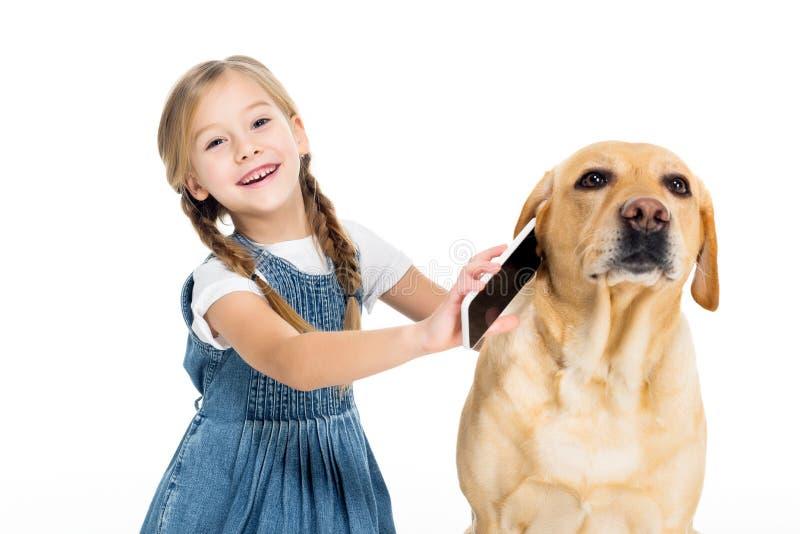 aanbiddelijk vrolijk kind die smartphone geven aan hond, stock afbeeldingen