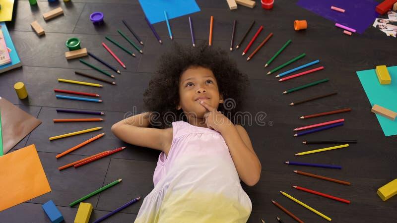 Aanbiddelijk weinig Afrikaans Amerikaans meisje die op vloer liggen en over vakantie denken stock foto