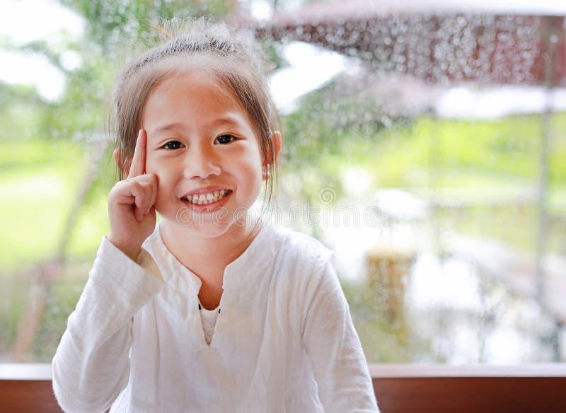 Aanbiddelijk weinig Aziatisch gebaar van het kindmeisje met positief grappig gezicht tegen glasvenster met waterdaling bij regena royalty-vrije stock foto's