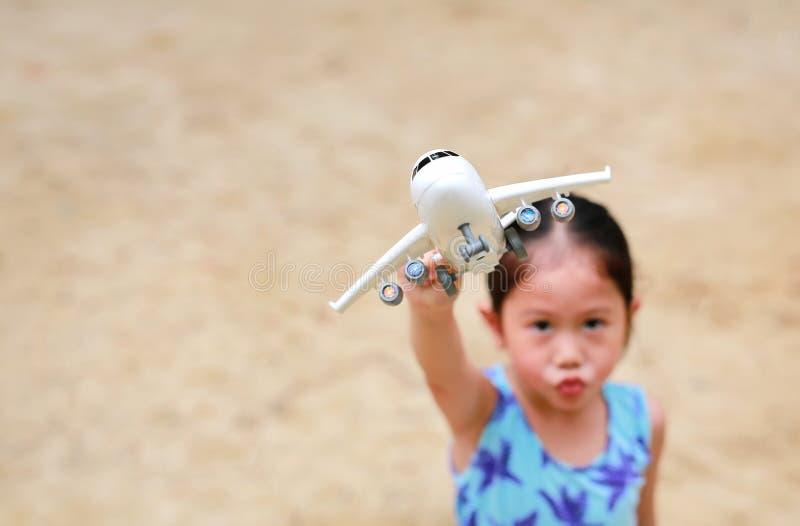 Aanbiddelijk weinig Aziatisch kindmeisje die met een stuk speelgoed vliegtuig in de tuin spelen stock fotografie