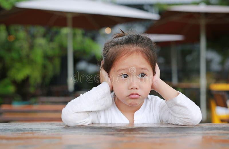 Aanbiddelijk weinig Aziatisch kindmeisje die op de houten lijst met uit het kijken liggen stock afbeelding
