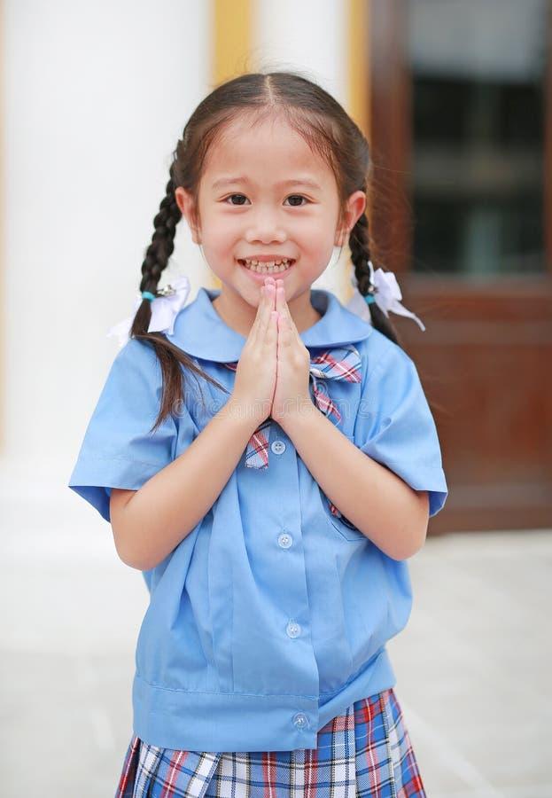 Aanbiddelijk is weinig Aziatisch meisje in eenvormige school loonseerbied Wai Thai Greetings stock afbeelding