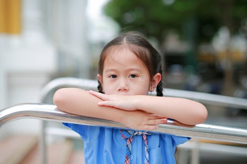 Aanbiddelijk weinig Aziatisch meisje in school het eenvormige speelse hangen bij metaaltraliewerk stock afbeelding