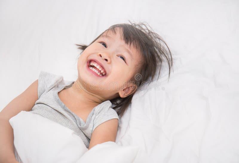 Aanbiddelijk weinig Aziatisch meisjeskielzog omhoog in haar bed stock afbeeldingen