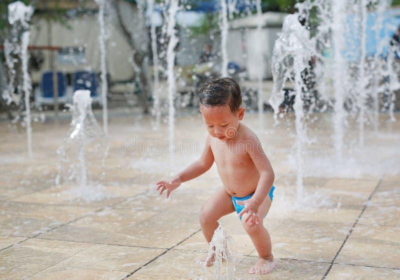 Aanbiddelijk weinig Aziatische babyjongen die pret op waterstroom hebben van een sproeier Jong geitje het spelen in speelplaatsfo royalty-vrije stock foto's