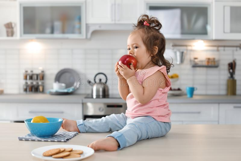 Aanbiddelijk weinig babymeisje die appel op lijst eten royalty-vrije stock foto's