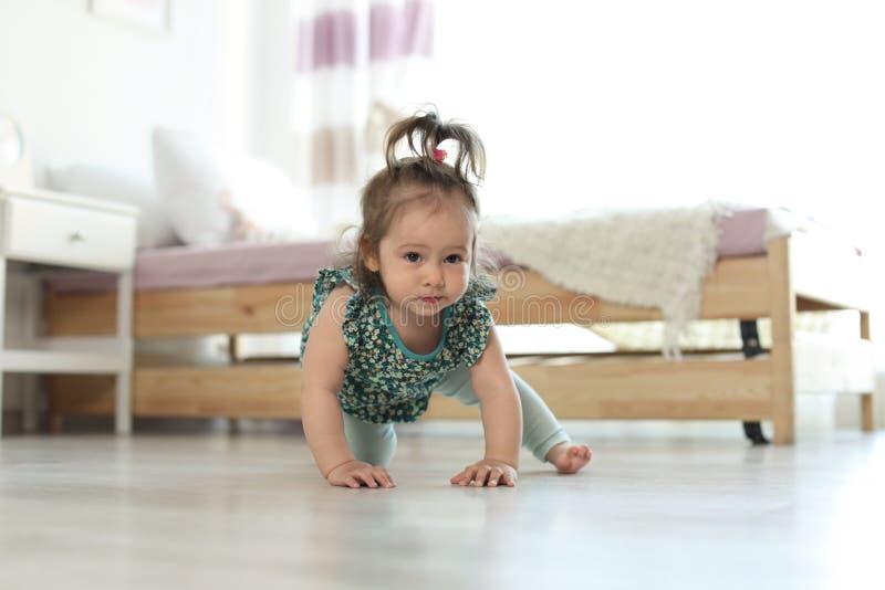 Aanbiddelijk weinig babymeisje die op vloer kruipen stock foto's