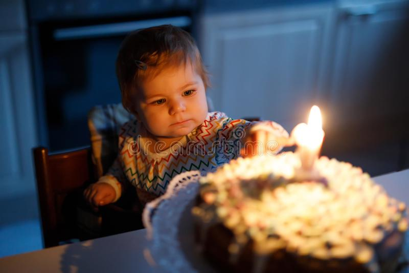 Aanbiddelijk weinig babymeisje het vieren eerste verjaardag Kind die één kaars op eigengemaakte gebakken cake blazen, binnen royalty-vrije stock fotografie