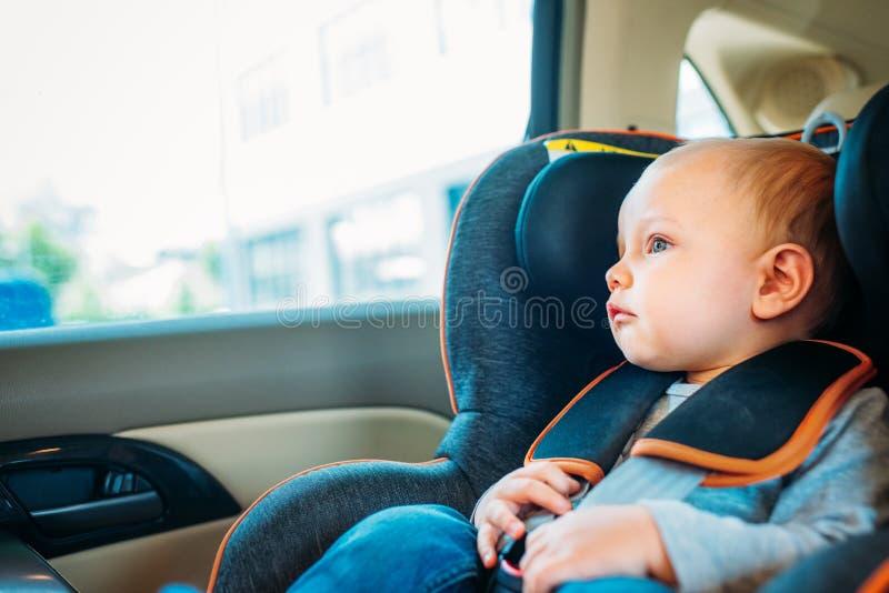 aanbiddelijk weinig babyzitting in kind stock afbeeldingen