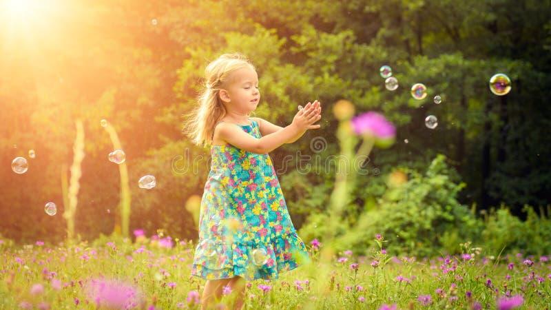 Aanbiddelijk weinig blond meisje die pret het spelen met zeepbels hebben stock fotografie