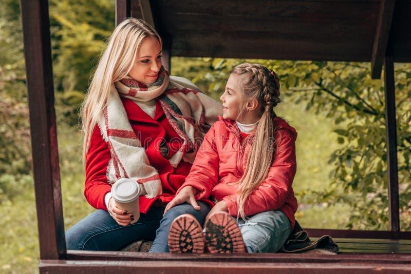 aanbiddelijk weinig dochter en gelukkige jonge moeder die met document kop elkaar glimlachen royalty-vrije stock afbeelding