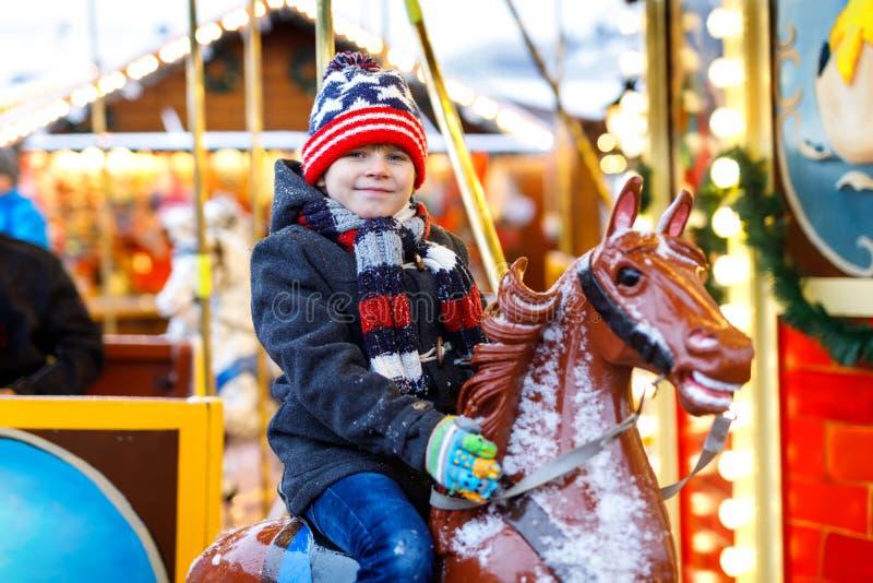 Aanbiddelijk weinig jong geitjejongen die op een carrouselpaard bij Kerstmis funfair of markt berijden, in openlucht stock afbeelding