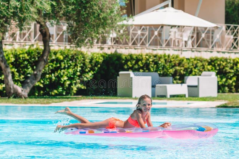 Aanbiddelijk weinig jong geitjespel in openlucht zwembad royalty-vrije stock foto