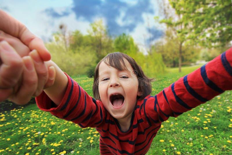 Aanbiddelijk weinig jongen, die in cirkel in het park spinnen, die pret met zijn mamma hebben, het lachen stock foto