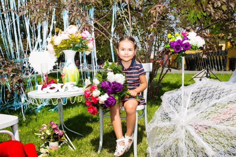 Aanbiddelijk weinig kazakh, Aziatisch kindmeisje op achtergrond van de de zomer de groene aard Bloemconcept en jong geitje stock fotografie