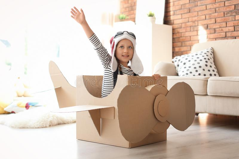 Aanbiddelijk weinig kind die met kartonvliegtuig spelen royalty-vrije stock foto