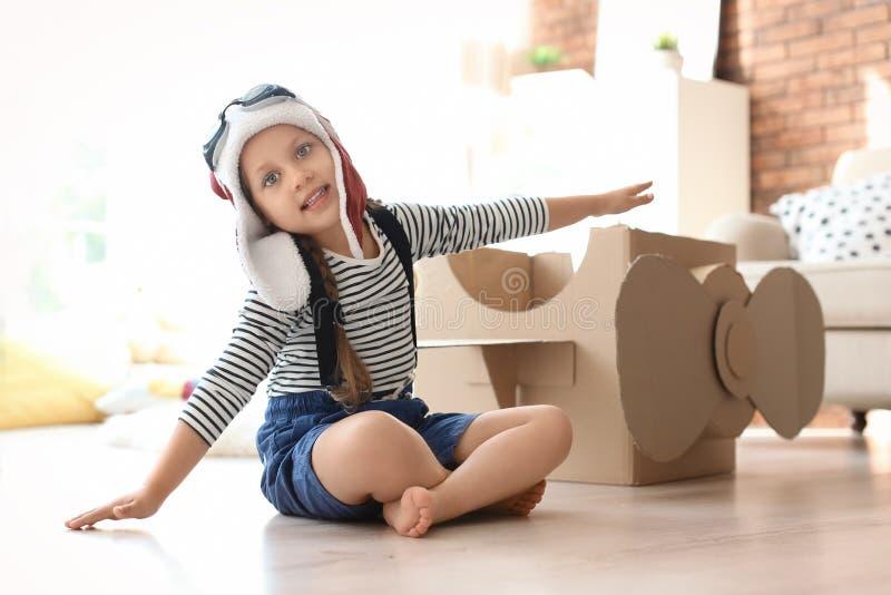 Aanbiddelijk weinig kind die met kartonvliegtuig spelen stock afbeeldingen