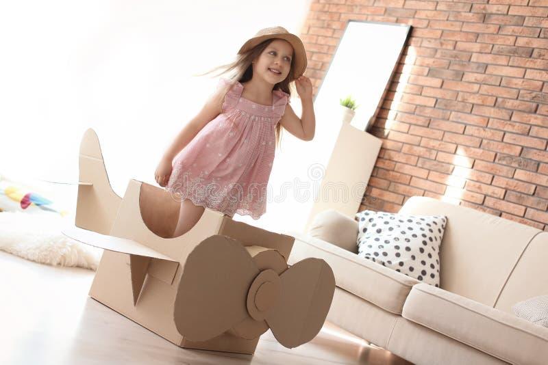 Aanbiddelijk weinig kind die met kartonvliegtuig spelen stock foto's