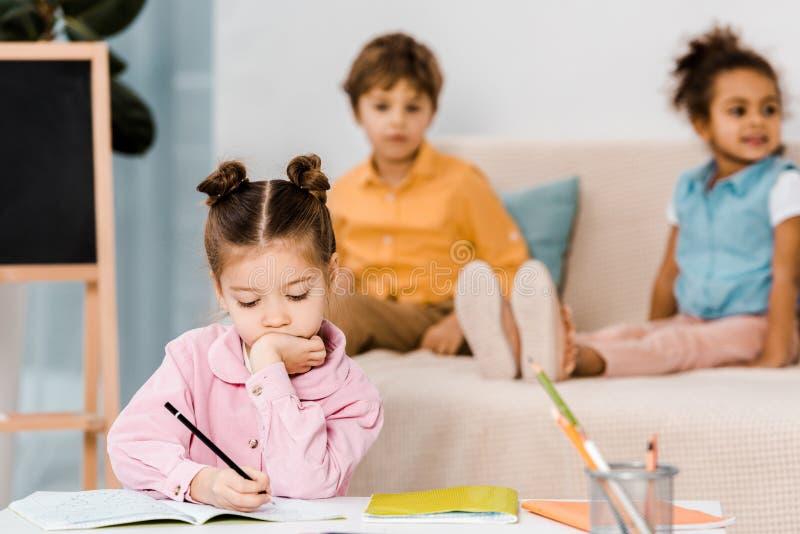 aanbiddelijk weinig kind die met potlood schrijven terwijl vrienden royalty-vrije stock foto's